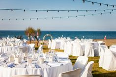 Wedding reception set-up with ceremony beach wedding set-p in the background. www.weddingincrete.com