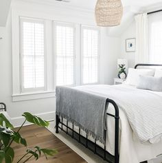 coastal bedroom decor, cottage bedroom decor with white walls, Black metal bed Black matte metal bed Featuring a black metal bed and comfortable white and grey linens, this bedroom exudes a timeless and inviting feel