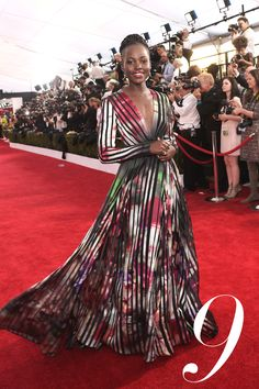 Lupita Nyong'o makes a major entrance in multi-colored, striped, full-skirted Elie Saab.   - HarpersBAZAAR.com
