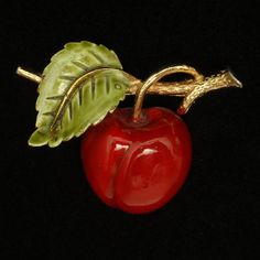 A pin that looks like single ready-to-eat cherry. The cherry has bright red enamel over gold tone metal with a green enamel leaf. This pin is in excellent condition. There are no marks or hallmarks. I