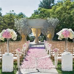 Pink Outdoor Ceremony -At the end of the aisle carpeted with blush rose petals, staggered white cherry blossom trees marked the spot where the couple exchanged vows.