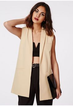 Give your wardrobe a bad ass boost with this impeccably fierce camel longline blazer. Keep things looking sharp and style this sleeveless longline blazer over a sheer button up shirt and high waisted skinny jeans. Featuring a long length la...