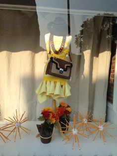 Our back to school window at Pebble Hill features a mannequin clad in a chic notebook paper dress, tortoiseshell necklace, Austrian felt hat, adorable handbag, surrounded by pencil balls.