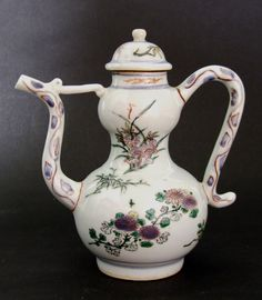 A Rare Transitional Porcelain Polychrome Double Gourd Ewer and Cover. This ewer is of double gourd form and is decorated in under-glaze cobalt blue with over-glaze enamel decoration of scattered plant sprays.The base has a four character Xuande mark. For a very similar Transitional ewer, possibly painted by the same hand, from the Butler Family Collection see : Shunzhi Porcelain, Treasures from an Unknown Reign (Butler, Curtis and Little, Art Services International 2002) page122 item 19.