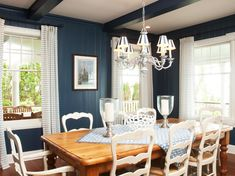 Blue wall paneling and ceiling beams provide a bold backdrop for the pine dining table in this country-style dining room. A painted chandelier, striped curtains and white dining chairs help tone down the saturated wall color, creating an overall look that is cozy.