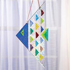 """Fused glass angelfish - North Carolina studio, a husband-and-wife team  pieces of hand-cut glass arranged on shimmering iridescent glass. Kiln-firing fuses the glass together. Comes with copper chain for hanging. 7.75"""" x 12.5"""". $79"""