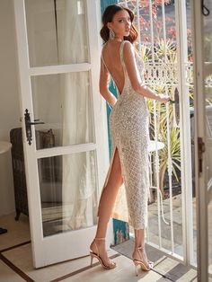 Ivory and silver hand embroidered column dress with a deep plunging v-neckline. The dress has floral and fishnet embroidery and scattered silver fringes
