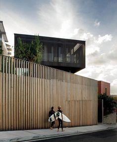 schlichter Raster aus vertikalen Holzbrettern für Zaun und Hausfassade