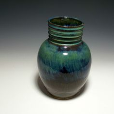 This unique item made from stoneware is beautiful as well as functional. It was created on the potters wheel from stoneware clay.   It has a dark nearly black glaze on the bottom and a blue/green glaze on top. It is perfect a a vase for fresh or dry floral arrangements.   It can also be used in the kitchen to hold your spoons.  Approximate measurements - Height - 7.5 inches