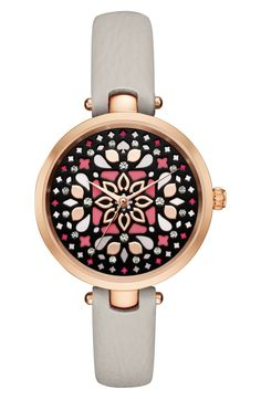 Glossy drops of color and sparkly crystals add brilliant life to the inky-black dial of this rosy polished watch set on a slender leather strap by Kate Spade.