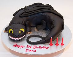 Toothless - How to train your Dragon - Chocolate fudge cake coated in dark chocolate ganache (with rice krispy treat head) and covered in fondant.