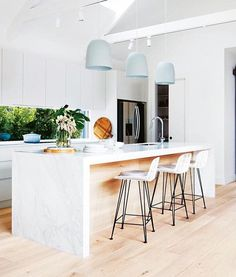 timber flooring Kitchen with pitched cathedral ceiling and exposed beams. A trio of large pendant lights hang over the white marble kitchen island. The glass splashback welcomes the outdoors in, and white cabinetry pairs with pale blonde timber flooring. Kitchen Interior, Kitchen Inspirations, Home Decor Kitchen, Kitchen Remodel, Kitchen Decor, White Marble Kitchen Island, New Kitchen, Home Kitchens, Marble Kitchen Island