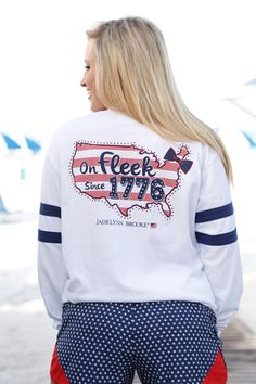 By Jadelynn Brooke, this On Fleek V-Neck jersey is white with Navy jersey stripes on the sleeves, and a flag on the front. Show off your American Pride all year