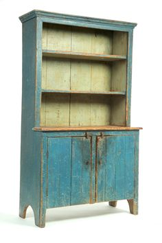 """OPEN-TOP CUPBOARD -    American, 1st half-19th century, pine. Diminutive size, one-piece cupboard with open upper shelves, beaded lower doors, and old blue paint. 63.5""""h. 36.5""""w. 17.5""""d."""