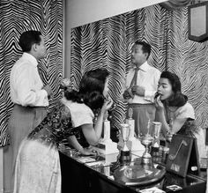 Billy Eckstine adjusting his tie while his wife June applies lipstick at a dressing table in their Manhattan apartment on April 11, 1950. The photo was taken by Martha Holmes, one of the first female staff photographers at LIFE magazin