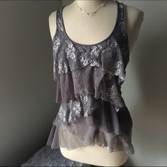 "Silver Gray Lace Waterfall Ruffle Sleeveless Top Lace has a way of adding simple elegance. And in my opinion it is versatile. Dress this up with a pencil skirt. Or a long lace tank under and leggings. It is 22"" at shorter point. And 26"" at longest. Slight racer back. Not lined. Wet Seal Tops Blouses"