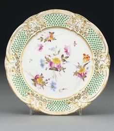A Nantgarw green-ground plate CIRCA 1820, IMPRESSED 3/NANT-GARW/C.W. MARK Painted with scattered loose bouquets and insects, within a lobed gilt scroll-moulded border painted with green oeil-de-perdrix pattern, within gilt rim 8½ in. (21.2 cm.) wide