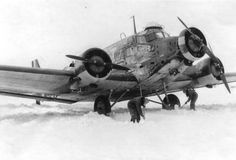 "Ju 52/3m ""GA+WW"" of 4./KGrzbV 900 in Roslawl during February 1942 prior to flying into the Demyansk Kessel (pocket). The crew of pilot Jürgen Pfau is seen shovelling snow away from the machine."