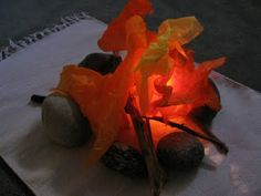 Campfire made out of stones, sticks and tissue paper. A flashlight tucked underneath creates a glowing effect.