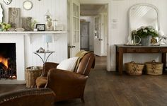 living room. love the mix of cottage white with worn leather and wood tones. Great plank floors, too.