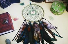 Traditional Celtic Dreamcatcher ans decor.  With natural feathers, emerald, forest, and olive green colors with celtic knot pendants, a druid spiral, and stone beading.  Also pictured: crystal bead stones, a celtic tree of life leather bound book, a green trinket box, and candle holders from Ireland.