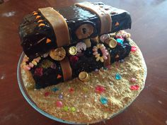 Treasure Chest Birthday Cake. Load full of edible treats. Sand is crushed graham crackers, jewels are broken jolly ranchers hard candies. Leather straps are caramels melted, and rolled out onto parchment paper, then cut into strips.