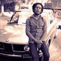 The handsome Bob Marley sitting on a car...