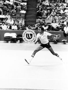 Tennis legend Arthur Ashe is photographed in action on the tennis court.