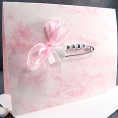 Oh Baby! Welcome the arrival of that newborn baby girl with this unique and adorable baby card that is made with an original diaper pin and alphabet letters spelling BABY. The diaper pin is placed on pink marble card stock. Every doting Grandma, Aunt or Friend is looking to