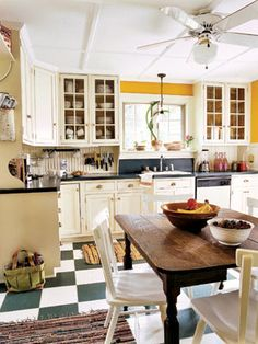 The checkerboard linoleum floor and bright yellow walls make this kitchen so inviting. #kitchens #decor
