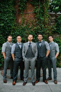 Groom in a suit, groomsmen in dark grey vests & light grey shirts