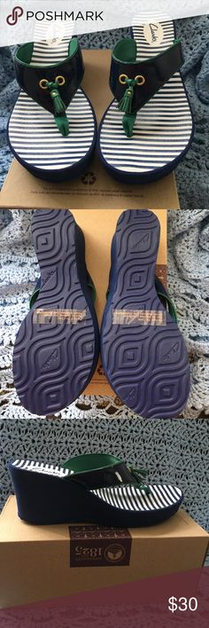 "Clarke Yacht Flash Navy Blue Thong Wedged Sandals Clarks Yacht Flash Sandals - US Size 6M Take the yacht to Stylishtown in this ritzy wedge slipper.  Beautiful nautical appeal. Comfortable padded footbed. Easy slip-on construction.  Synthetic patent leather upper with beautiful sheen detailing.  Stitched toe post Decorative tassel adorns the front Smooth synthetic lining Platform wedge heel Textured synthetic outsole Heel height:  2 3/4"" New In Box but the box top is missing Clarks Shoes…"