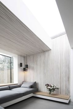 """Ash timber slats create zoning of the sitting area and wrap up and over the ceiling,"" they added.""These disappear into a seamless skylight."""
