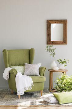 Zona de estar con paredes y alfombra grises y una butaca en verde_00451369
