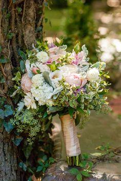 Bride's bouquet with bush, peach, greenery, white and lavender.   Romantic garden wedding ideas.   Photographer: Trinity Ridge Photography  Venue: St Catherine's at Bell Gable  Fayetteville, Arkansas Wedding Florist