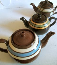 These three vintage teapots are classic English Redware, sometimes referred to as 'Brown Betty' teapots.