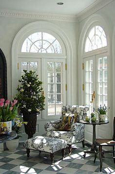 Beautiful sun room. Floor to ceiling windows, Georgian style.  Black & white floor, wingback chair & footstool covered in Toile de Jouy fabric, pot plants. .