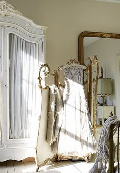 Curvy white armoire, gilded Victorian screen and that huge Louis Philippe (?) mirror. Charming antique elements from different periods that create a romantic ambiance in the bedroom.