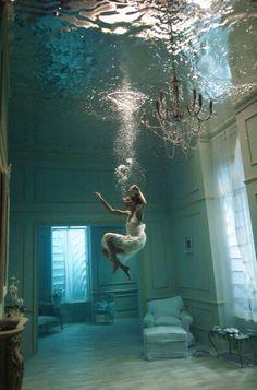 Girl in dress underwater in room with chandelier