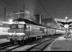 """The Paris-Nîmes night train is getting prepared in Paris for its long trip straight to the south 'Moret - Nevers - Clermont Fd) and the long and beautiful Cévennes line (Clermont Ferrand - Nîmes). In 1984, the Paris-Clermont line was not yet electrified, thus a diesel took the train from Paris. The first passenger car behind the engine is an antique """"Bacalan"""" car, fitted with 11 compartments of 8 seated passengers each: not very comfortable car for travelling long distances."""