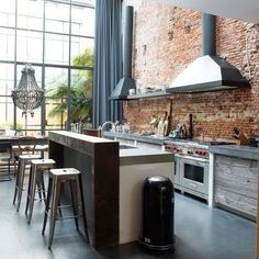 reclaimed timber, smooth concrete worktops and clean stainless-steel- industrial kitchen with a rough, rustic edge More