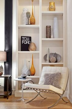 Have a minimalist approach with shelves, stand books upright, tall vases, objects of various colour and height will give personality