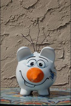 Disney frozen hand painted piggy bank Free hand. 3D crafted nose and sticks to lol like Olaf. Painted by April ziviello on Facebook April's showers custom creations.