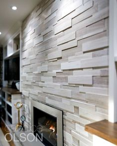 A beautiful wall of stacked-stone veneer. The stone says permanence, and the fire is welcoming; a universal symbol of home. A beautiful wall of stacked-stone veneer. The stone says permanence, and the fire is welcoming; a universal symbol of home. Modern Fireplace Tiles, Modern Stone Fireplace, Stacked Stone Fireplaces, Fireplace Tile Surround, Home Fireplace, Fireplace Remodel, Fireplace Surrounds, Fireplace Design, Brick Fireplace