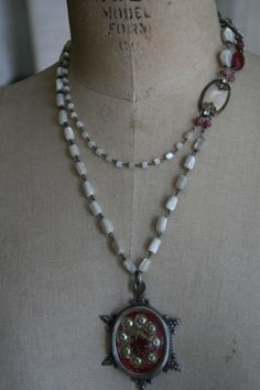 This is a fabulous piece. A large vintage French relic hangs from the middle of this double mother of pearl necklace. Semi-precious gemstones are wire wrapped to a beautiful vintage paste hook. The longest chain is approx. 20 in length and the shorter one is approx.18 in length.