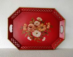 Vintage serving tray by E. T. Nash Company, New York, ca. 1950s. 20 x 15 x 1.5.  Red painted metal with punchwork sides, gold rim, and hand painted floral motif in the center featuring roses and daisies. The bouquet colors include muted shades of off white, pinkish taupe, yellow, and green. The label on back reads Hand Painted, Chip and Alcohol Resistant. The paint is not sealed, however, and the painted center design has chipped in places consistent with age and use. Decorative use is…