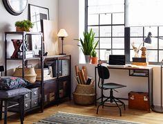 Espacio de trabajo con suelo de madera, estantería y escritorio de metal negro y madera, con estilo industrial.