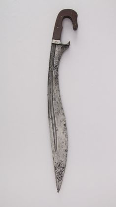 Knife (Falcata) Date: possibly 2nd–4th century Culture: Iberian Medium: Steel, wood Dimensions: H. 20 15/16 in. (53.2 cm); H. of blade 17 in. (43.2 cm); W. 2 5/8 in. (6.7 cm); D. 13/16 in. (2.1 cm); Wt. 1 lb. 0.7 oz. (473.4 g) Classification: Knives