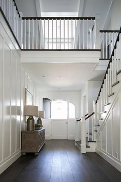 Two story foyer features full wall board and batten trim lined with a distressed cabinet topped ...