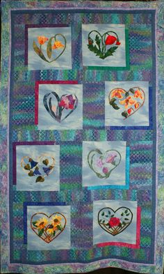 "1013-HeartsAndVines.jpg - 1013Pat Harrington, Jeanne Allison, Sandy Anderson, Elaine Bishop, Cindy Cochran, Rhonda Kondo, Dottie Pope, Lenee Smith, Glenda Warren, Trena Gay Wheatcraft, Luti Wright, Marilyn Yeakey - Hearts And Vines -- Appliquéd Quilt - 2 or more persons. Exhibit Only. 44x72"". Hand Appliquéd, 2009. Machine quilted by Cynthia Clark. Hearts and Flowers by Kathy Delaney."